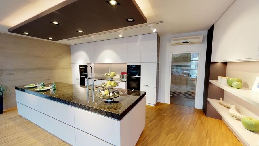Moderne Küche mit griffloser Insel und ausfahrbarer Barplatte